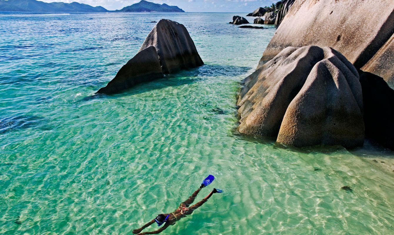 Woman snorkeling in clear water amongst granite boulders.