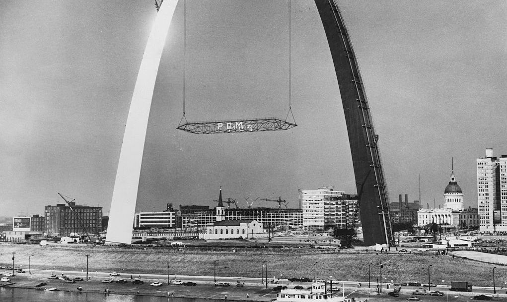 The Gateway Arch monument under construction in St. Louis, Missouri, USA, circa 1964. Creeper derricks are placing a temporary scissors truss between the partially completed legs at 530 feet (160 m) in order to steady them. The 630-foot (192 m) inverted catenary arch was designed by Finnish American architect Eero Saarinen.
