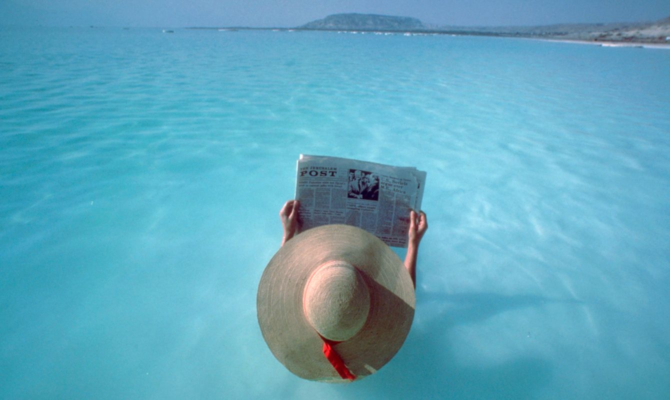 A tourist floats and reads The Jerusalem Post in the Dead Sea | Location: Ein Bokek Oasis, Israel.