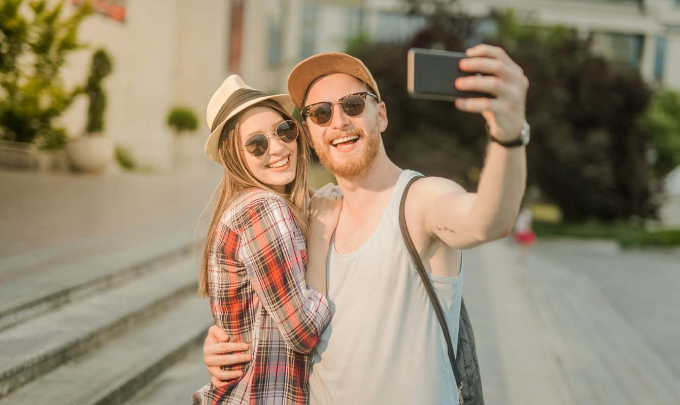 Happy young couple taking a selfie together on a summer day