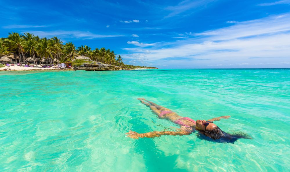 young woman relaxing in turquoise waters of Caribbean Sea in front of paradise beach in Tulum, close to Cancun