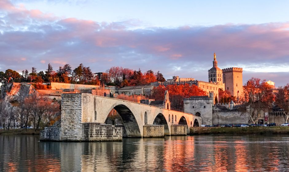 view of Pont Saint-Bénezet(Pont d'Avignon) and the medieval castle/walls in the sunset time in fall in Avignon, France.