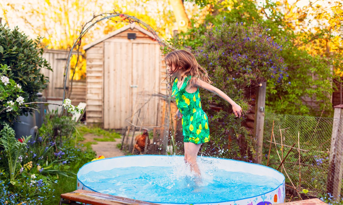 A young girl cooling off by splashing in a paddling pool in a back garden.