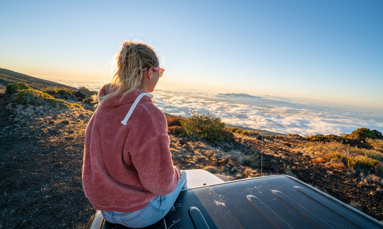 Young woman sitting on vehicle on a volcano and looking at sun setting over the cloudscape
