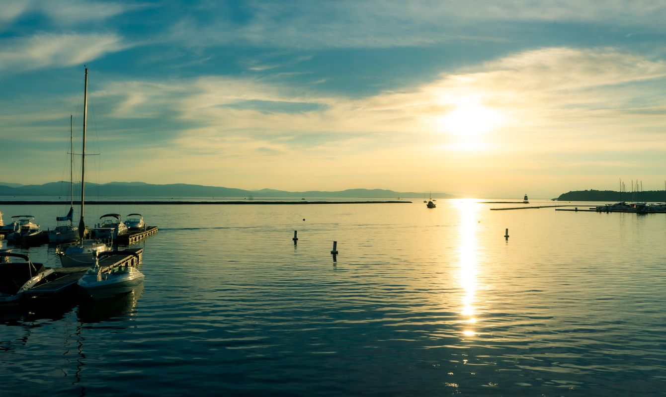 sunset on lake champlain in burlington vermont with boats in the harbor