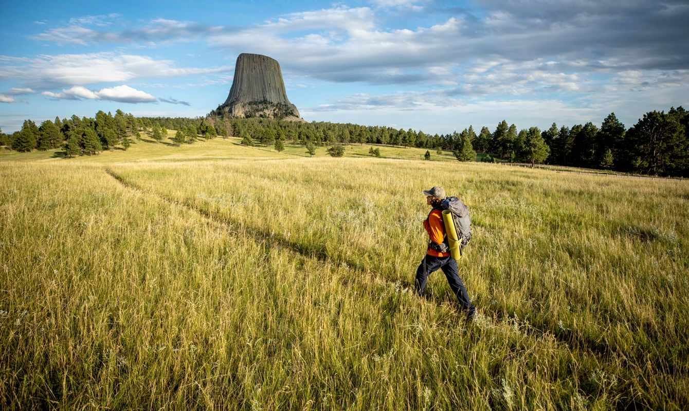 Image of a hiker walking with a backpack towards Devils Tower National Natural Monument in Wyoming.