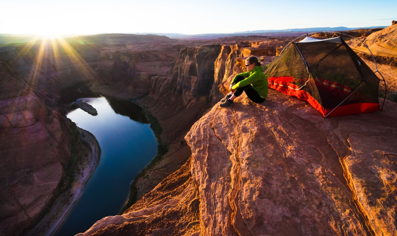 A woman overlooks the Colorado River from a campsite on the edge of Marble Canyon in northern Arizona.