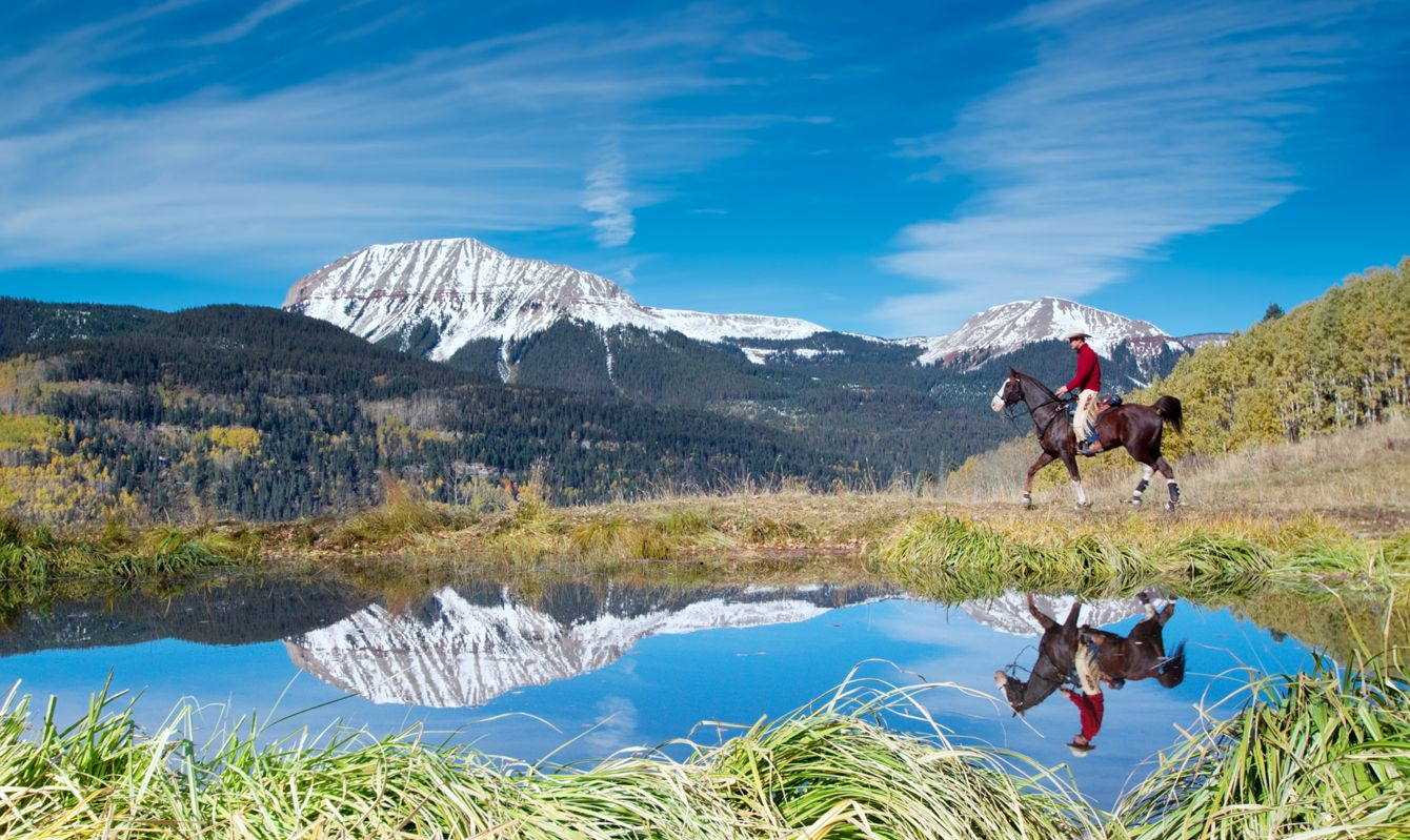 man horseback riding is reflected in the water of a pond with snowcapped rugged mountain peaks in the background. such beautiful nature scenery and outdoor sports and recreation can be found in the san juan range of the colorado rocky mountains, durango. horizontal composition.