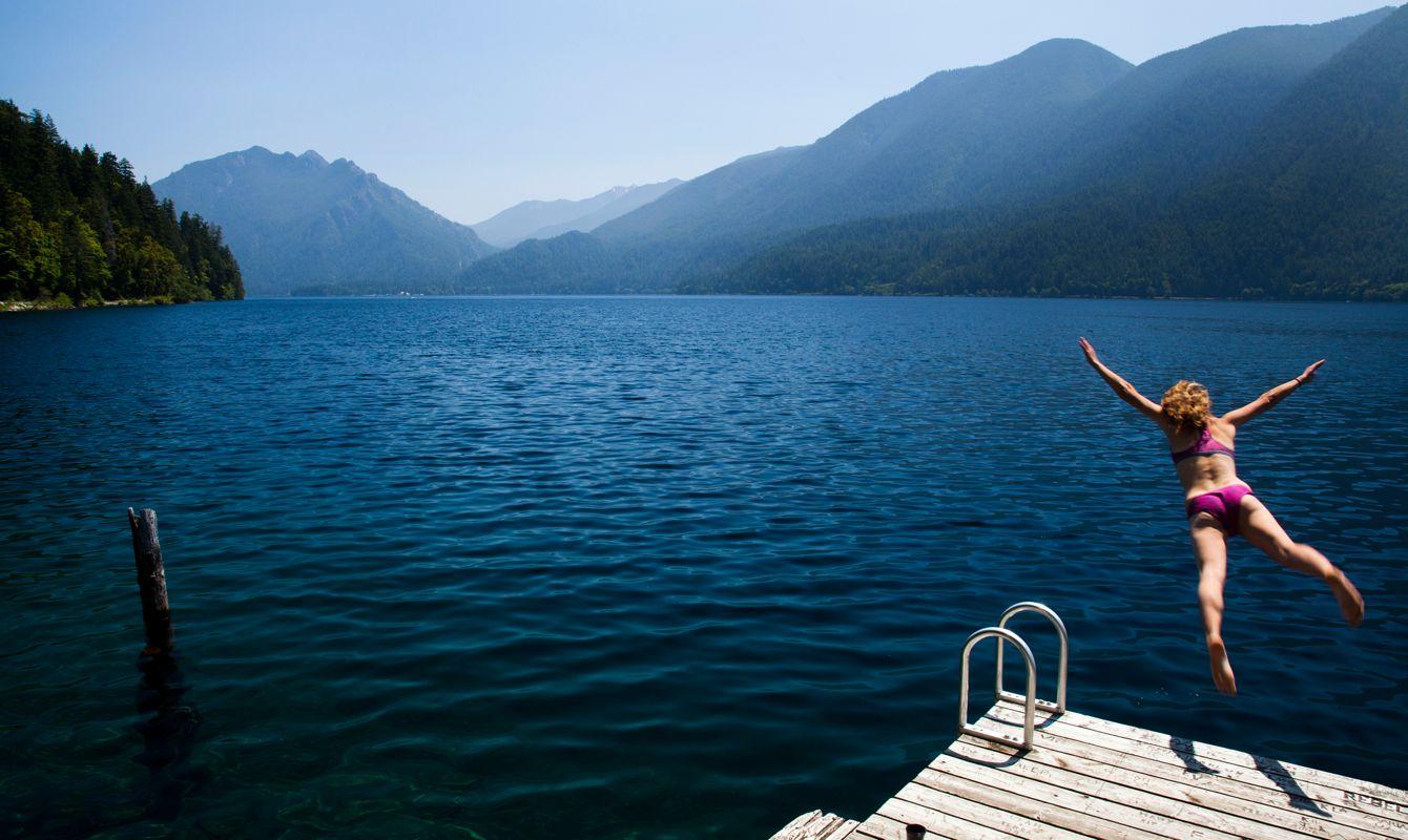 USA, Washington, Olympic National Park, Woman jumping to lake