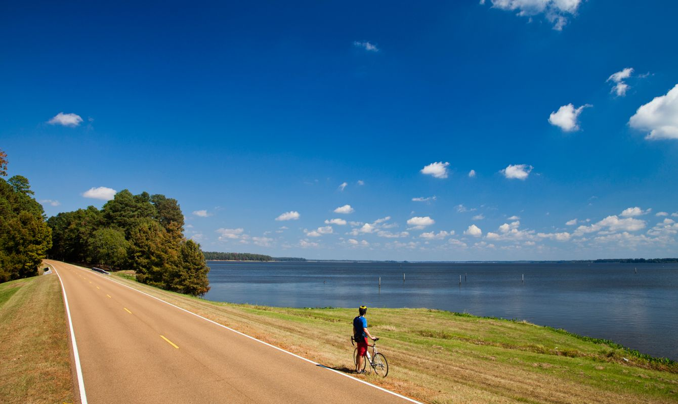 A young man, athletic and fit, rides his road bike on the sunny day, Natchez, Mississippi, USA