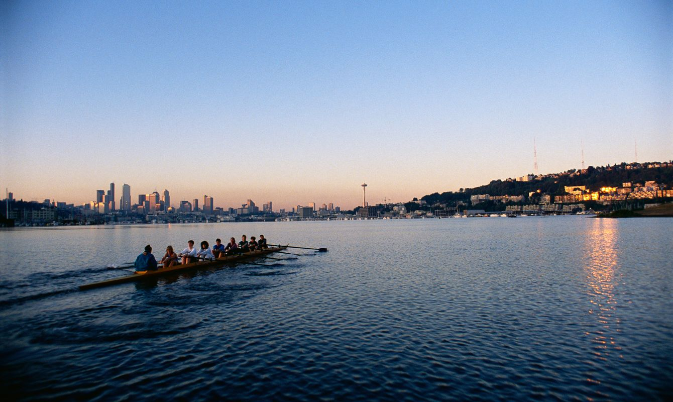 Women's rowing team, from the Lake Washington Rowing Club, practicing in an eight oared racing shell, on Lake Union at sunrise, with a view of downtown Seattle, Washington.