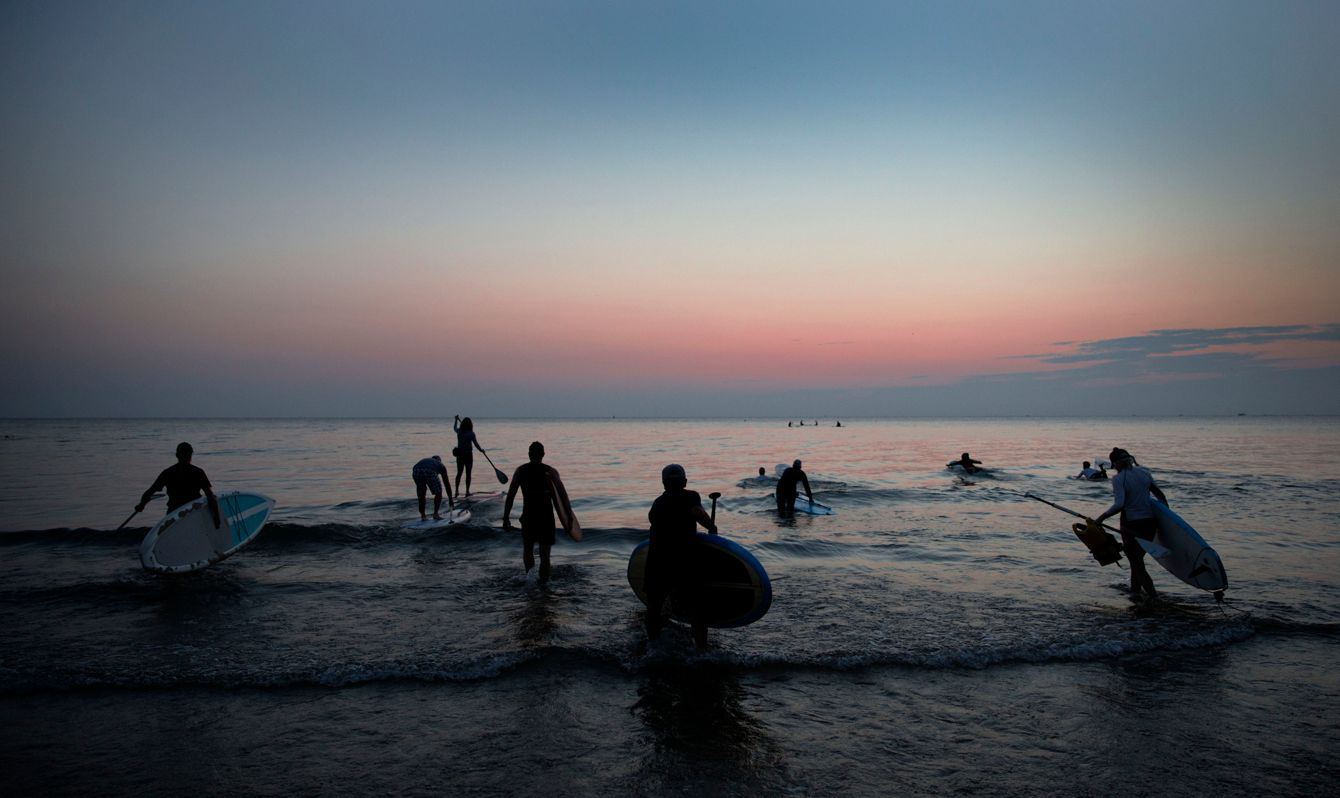 A group of paddleboarders head out enmass to experience the dawning of the day on Lake Michigan.