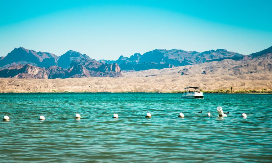 Colorado river at Lake Havasu City scenic mountainous summer landscape background. White buoys and boat silhouette in clean water. Vintage filter with muted blue green, earthy yellow and brown colours