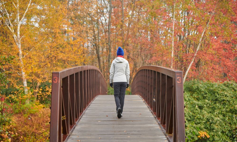 Woman hiking at Stowe Recreation Path on autumn day in Vermont, USA.