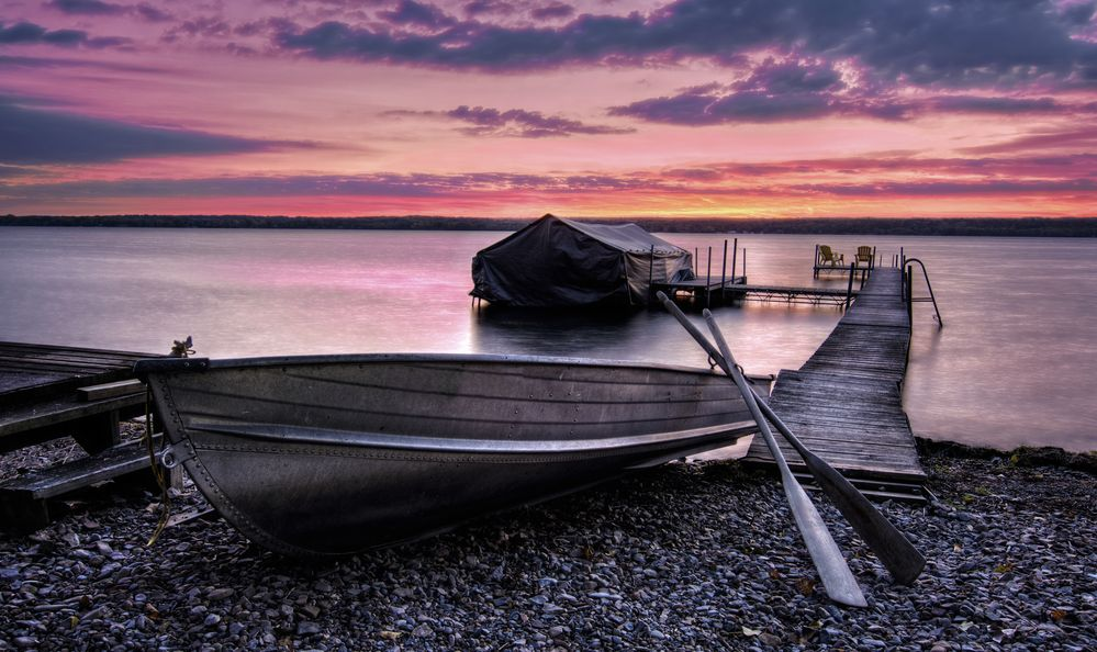 A beautiful sunrise on the shores of Lake Cayuga, Finger lakes region of New York state. A row boat sits on the side of a pier that leads out to a boat shelter and a deck for watching the sunrise.