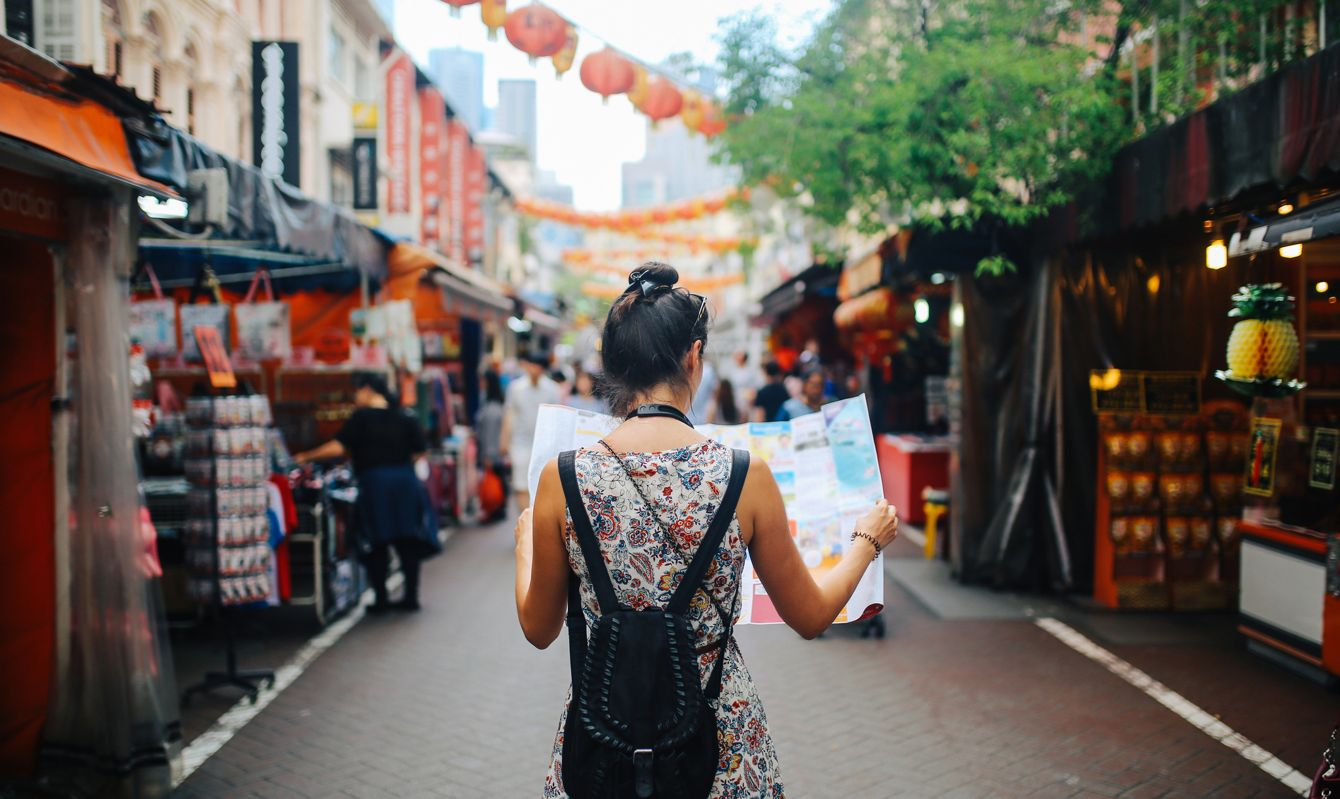 Rear view image of a young brunette woman. She is enjoying the walk and exploring the city, wearing a casual but fashionable dress, sightseeing and shopping on the Singapore street market. She is holding a large city map, checking out where to go next.