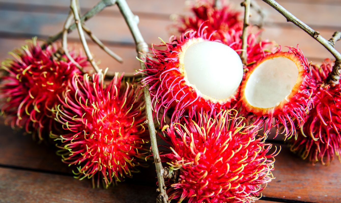 Half-separated rambutan from a skin on a wooden table among whole fruits.