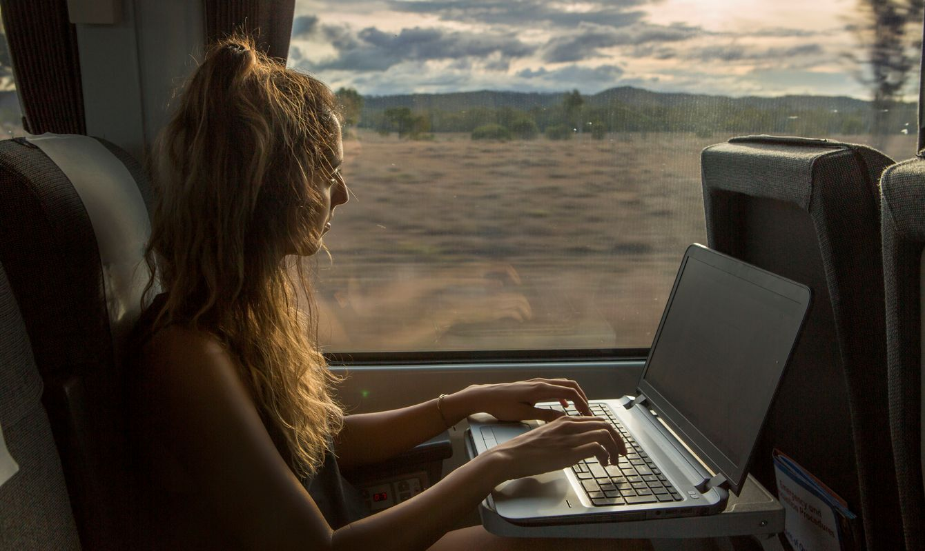 The Queensland Rail services most of the coastal areas in the Queensland territory. A woman works on her laptop while traveling.