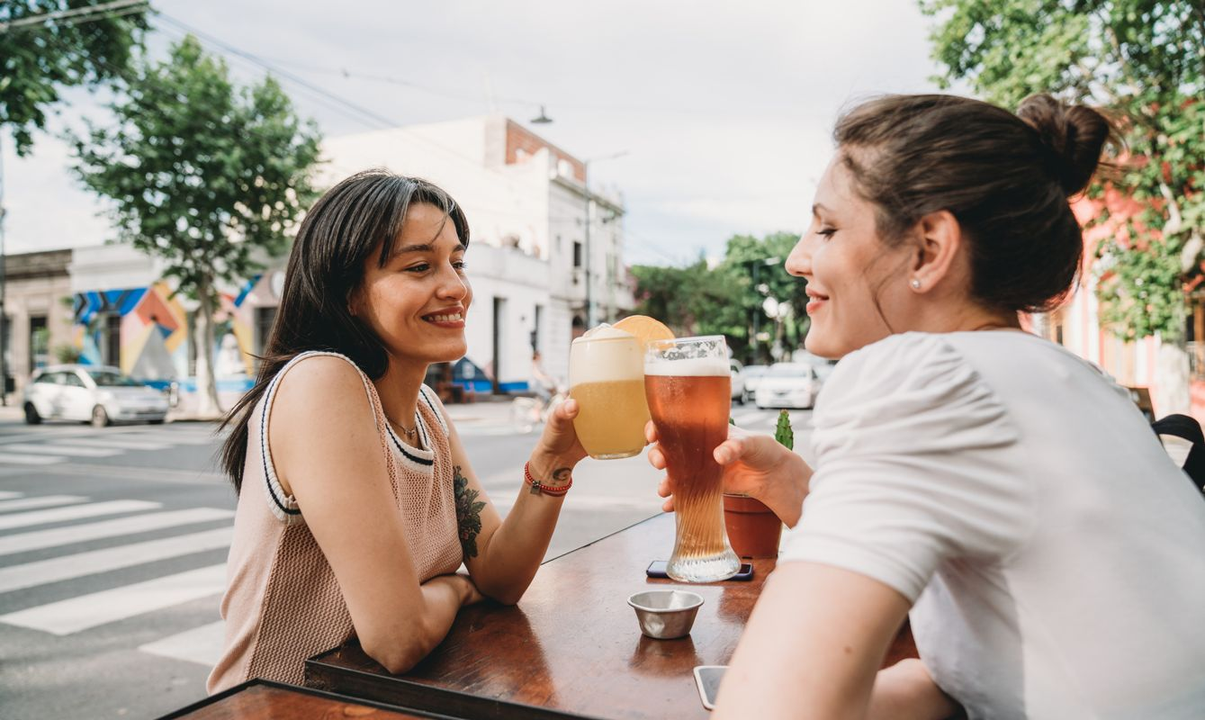 Two women friends sitting at a cafe, doing a celebratory toast together. They are drinking beer and cocktails. They are having fun together. Hispanic and caucasian ethnicities.