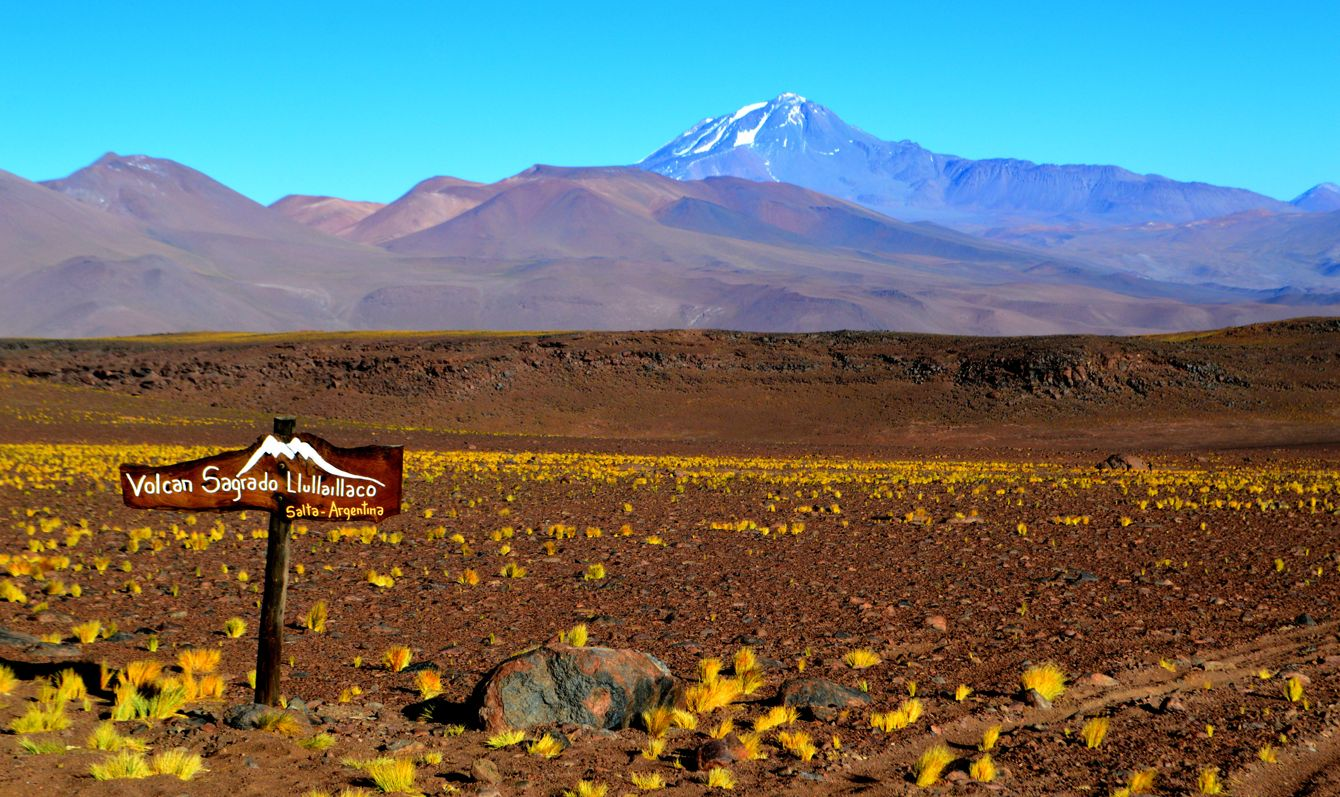 """Llullaillaco volcano, the sacred volcano. The sign says: """"Llullaillaco sacred volcano, Salta, Argentina"""". Andes, Salta, Argentina"""
