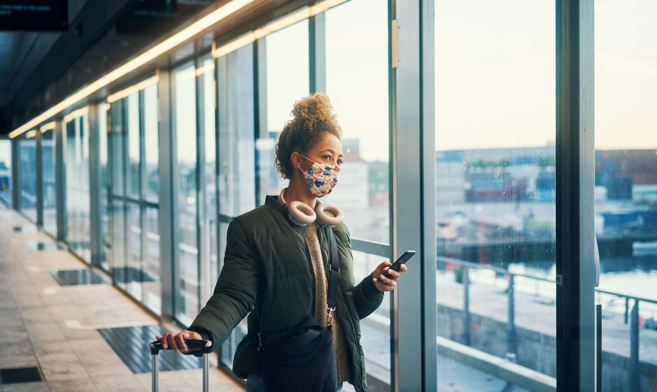 Shot of a masked young woman using a smartphone while travelling through a subway station