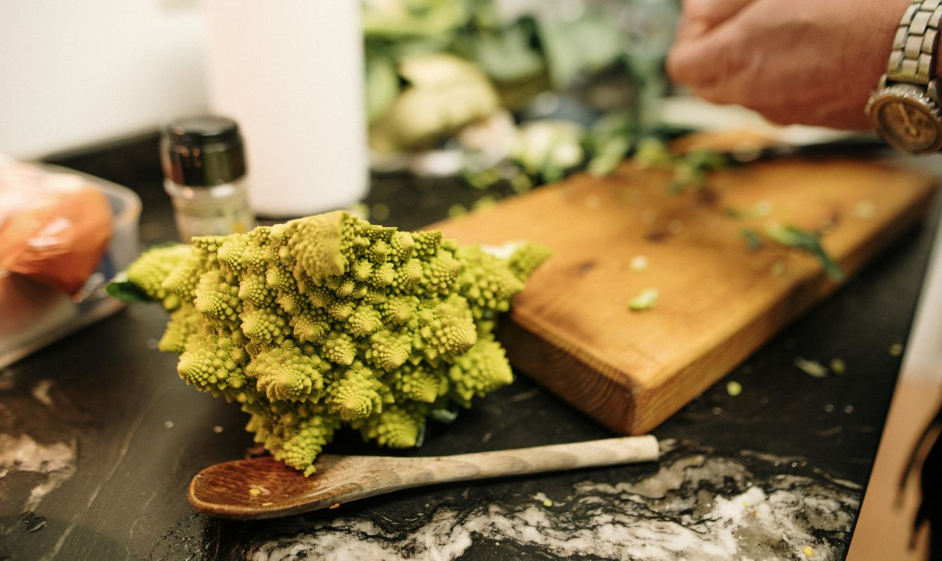 A Romanesco Broccoli being cut and cooked in a kitchen