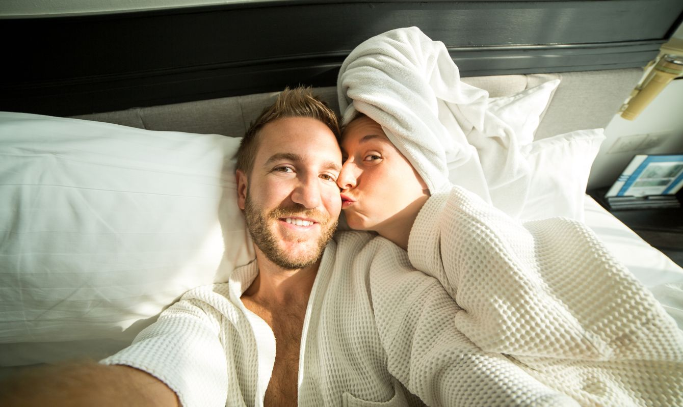 Young funny couple on a comfortable bed in an hotel room taking a selfie in the morning. They both wearing a bathrobe and the woman a towel on her hair.