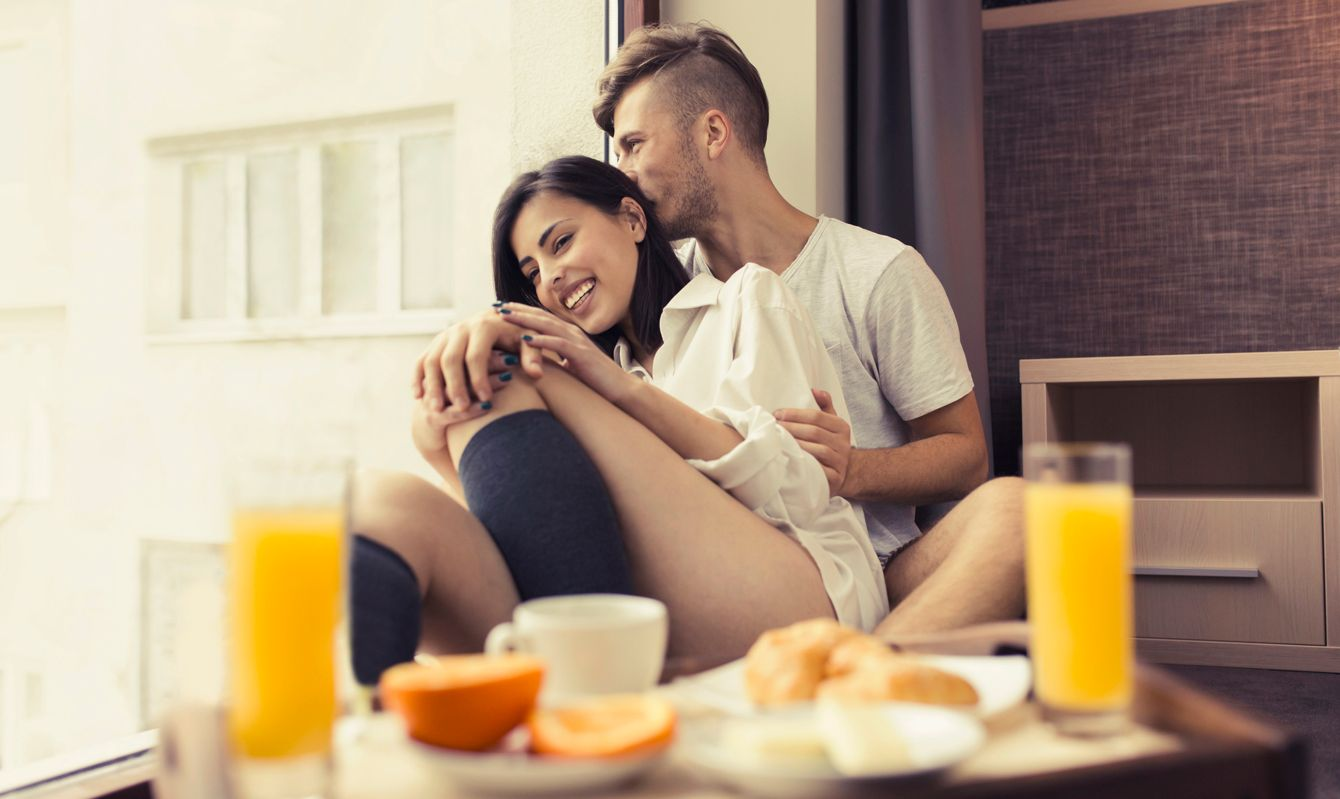 Beautiful young couple sitting by the window embraced, enjoying their carefree weekend morning together. Wooden tray with breakfast on it in front of them.