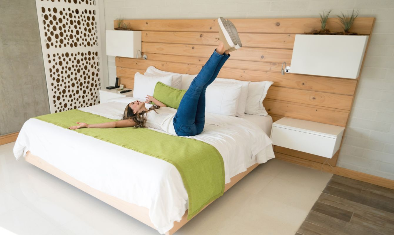 Excited traveling woman in her room at the hotel jumping on the bed and looking at the camera smiling