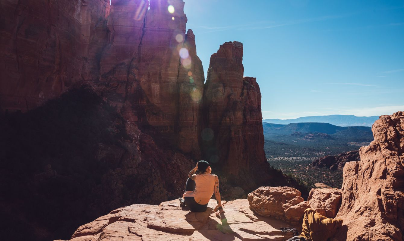 Woman sitting on a cliff in Sedona, AZ