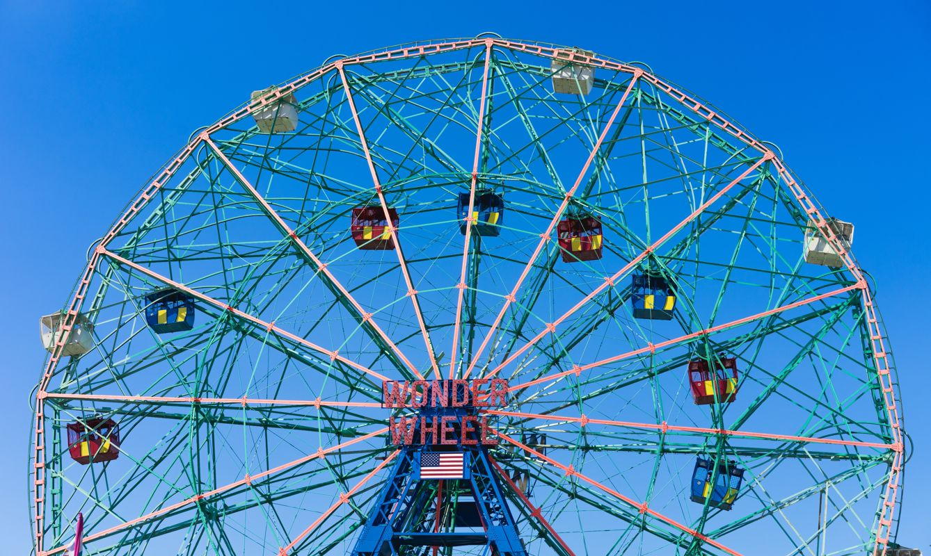 Coney island - pink and white ferris wheel under blue sky at day