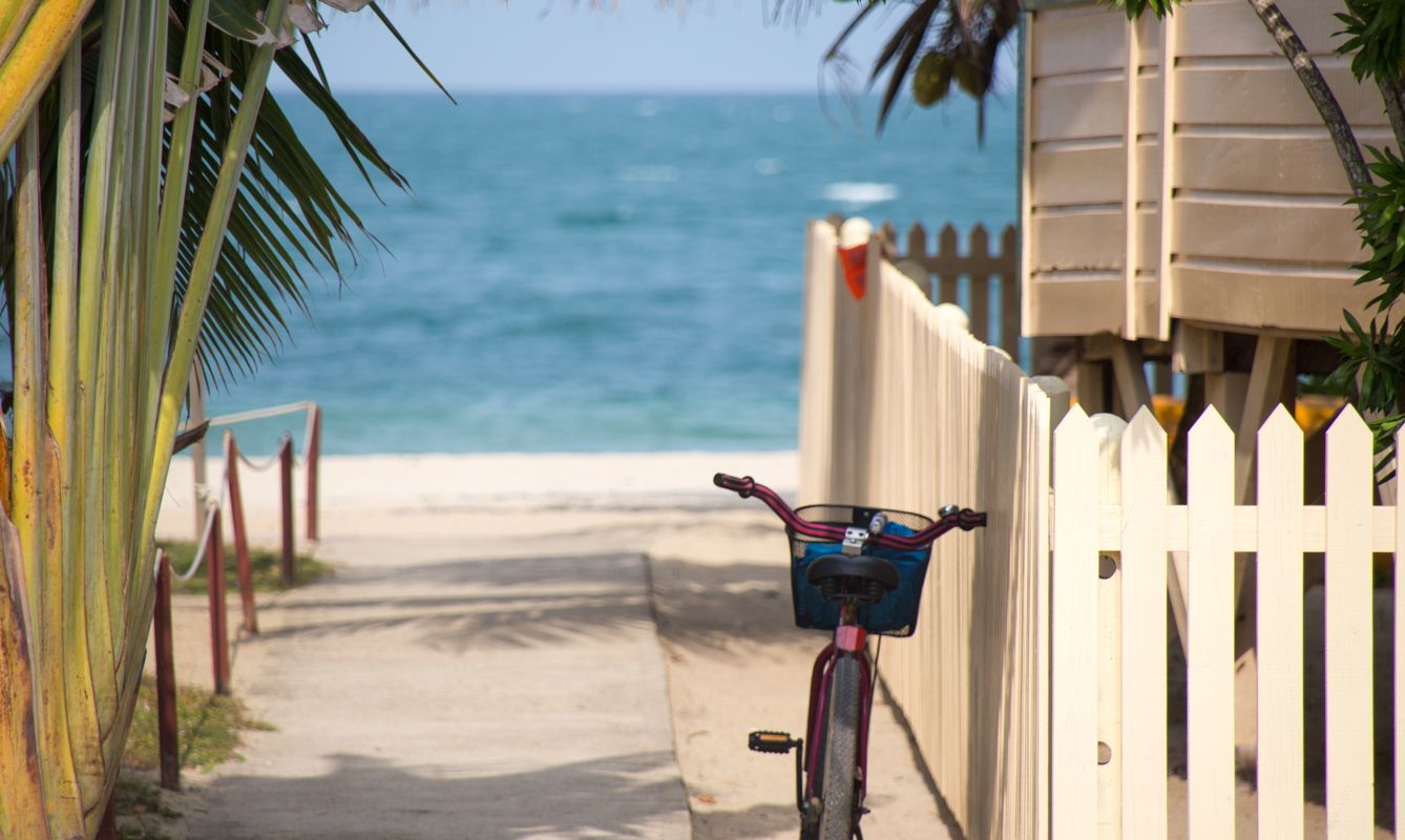 Key West, Florida: A cute beach bicycle rests against a beach house fence, facing the sea and a sandy beach somewhere in the Florida Keys.
