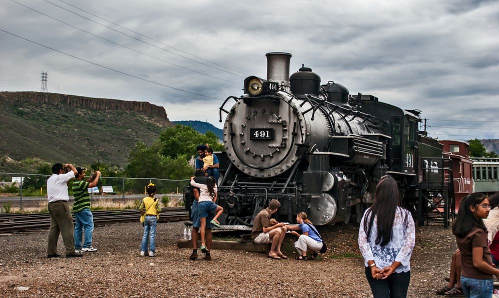 People gathered around and ancient locomotive railway engine which was built in 1902 in the Colorado Railroad Museum complex