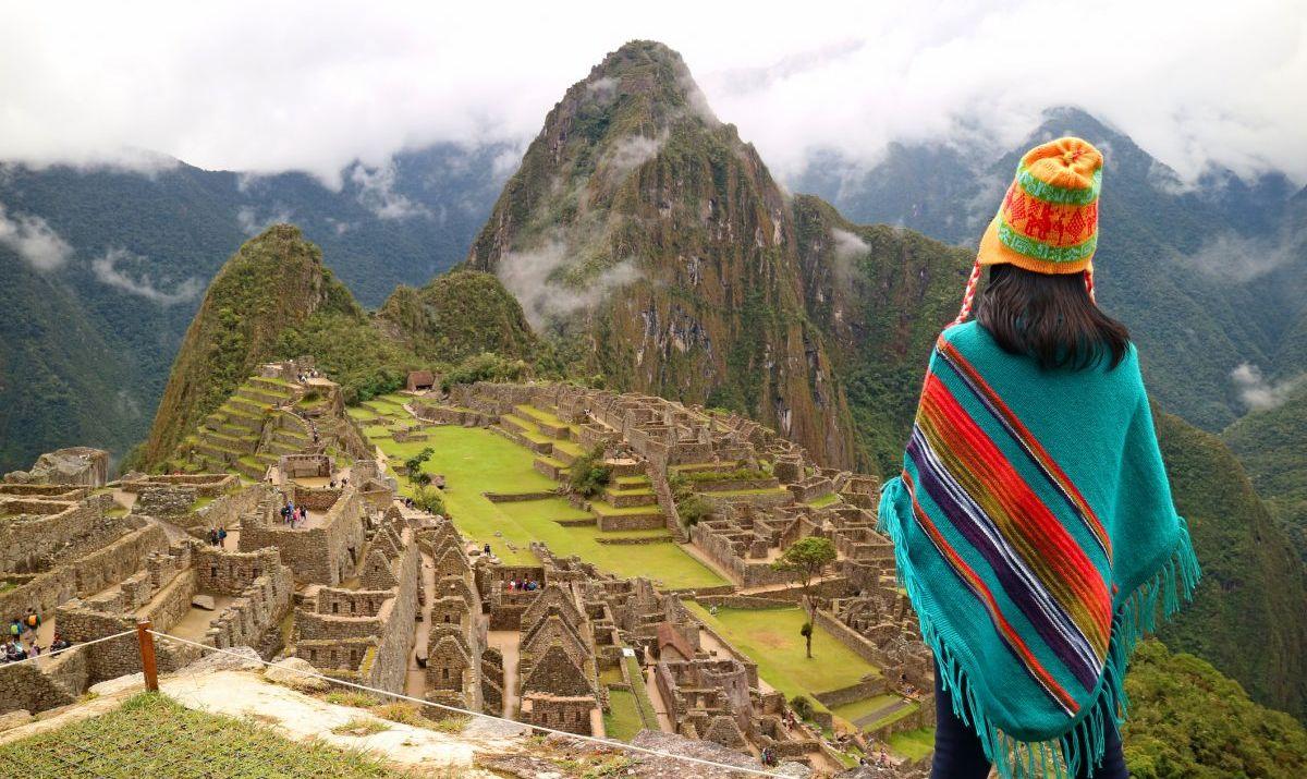 Girl In Peruvian Shawl Looks Down On Machu Picchu