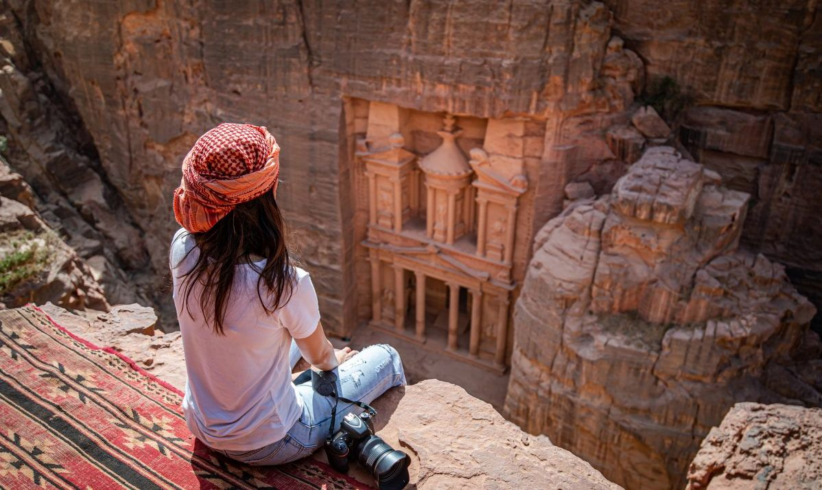 Woman Looks Down At Petra From Cave