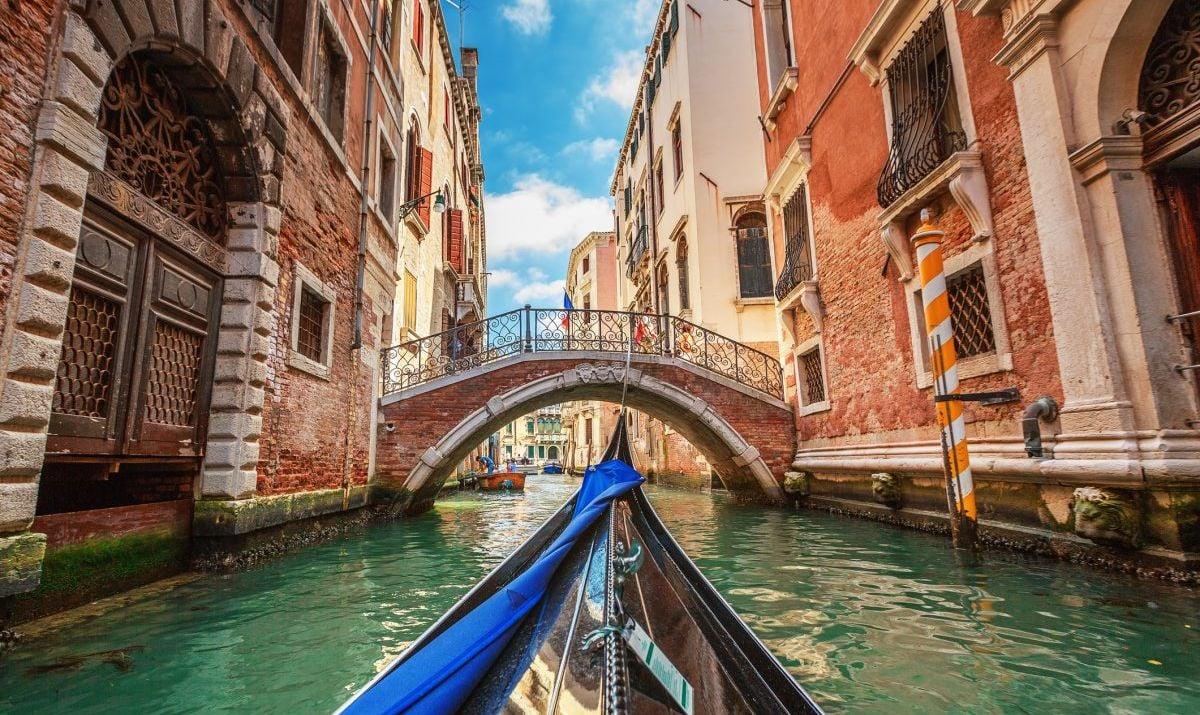 Gondola Points Under Bridge In Venice Canal