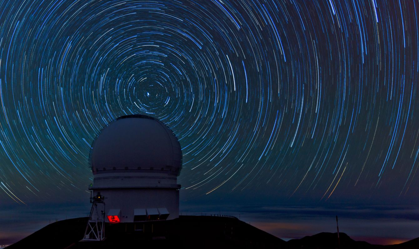 Spring Hawaii Big Island, Mauna Kea, Star trails with Canada-France-Hawaii telescope in foreground night shot, long exposure.