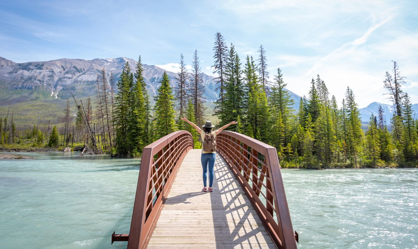 Young Woman with Arms raised Looking at Vermilion River from a bridge in Kootenay National Park, British Columbia, Canada