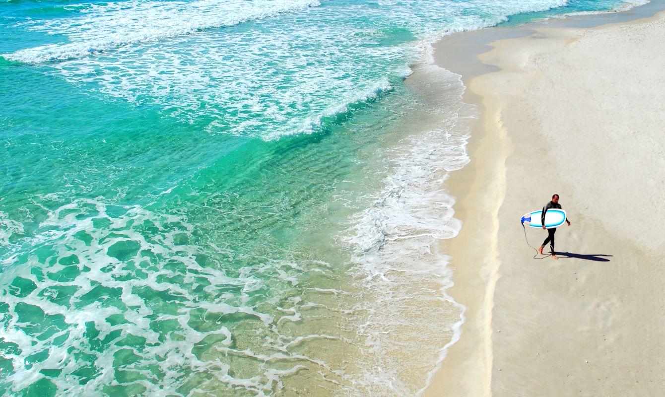 Lone surfer walking on deserted beach next to beautiful ocean