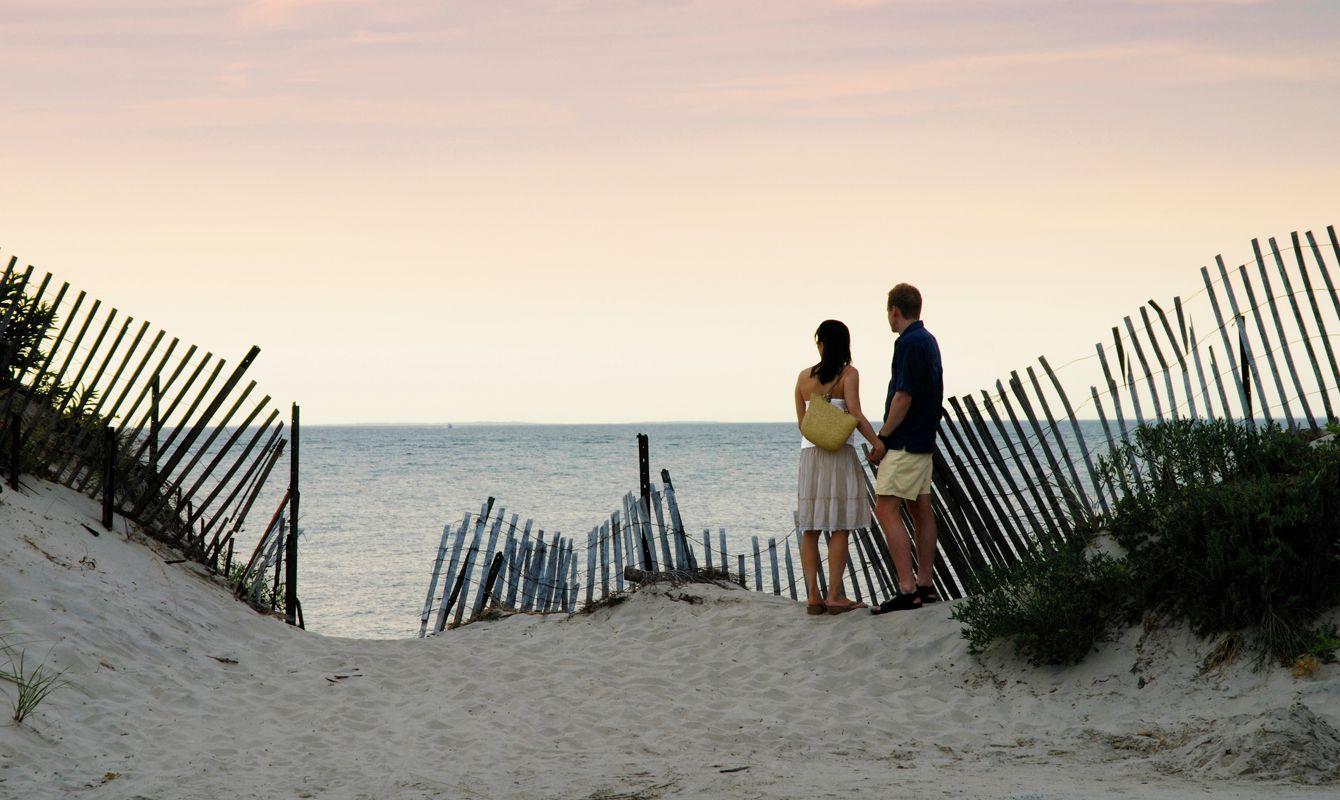 Couple at beach, rear view, dusk