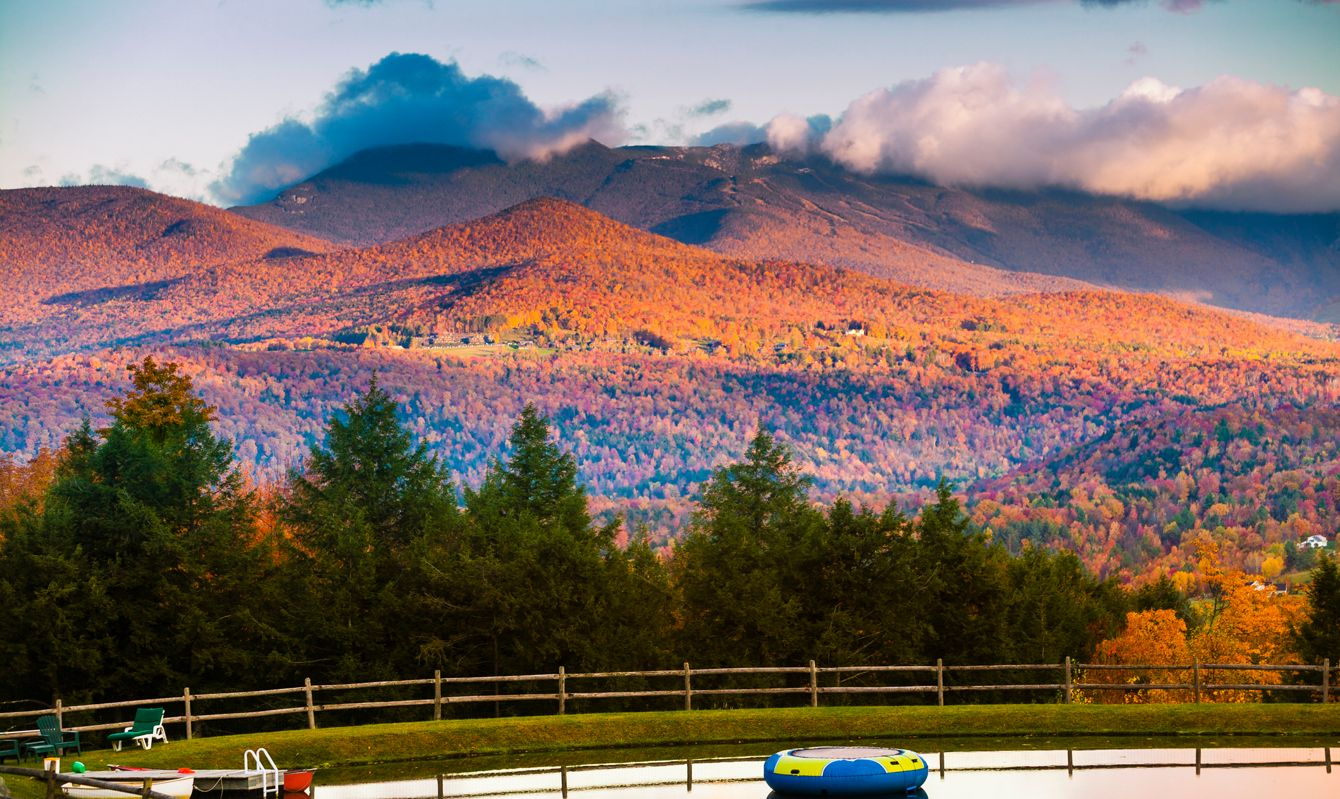 Overlooking a swimming pond with Mt. Mansfield during fall foliage in the background, Stowe, Vermont, USA