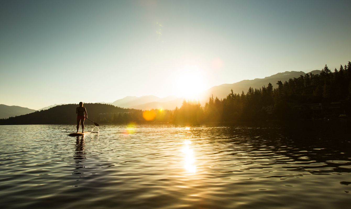 Silhouette of young Asian female paddle boarding in calm waters.
