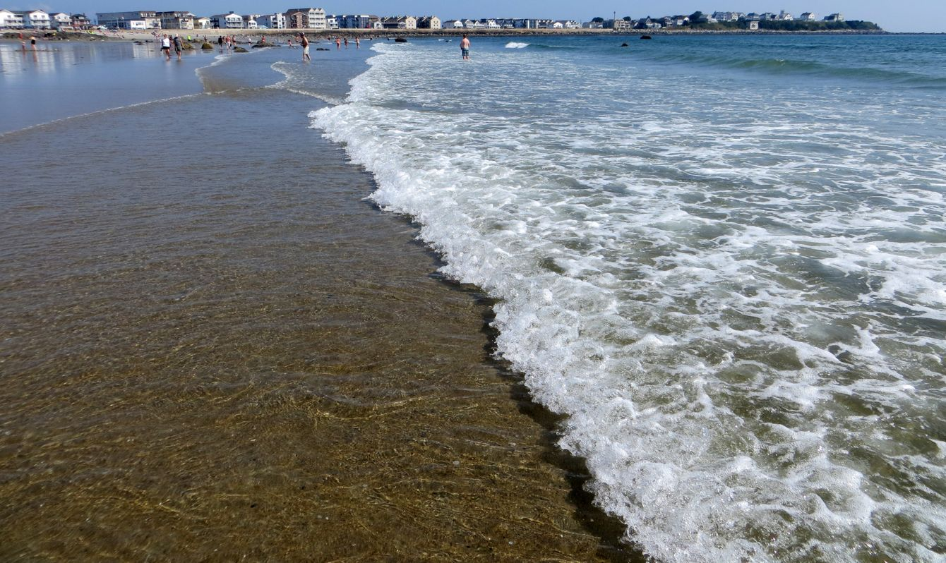 View of Hampton Beach, New Hampshire with surf breaking up on shoreline.