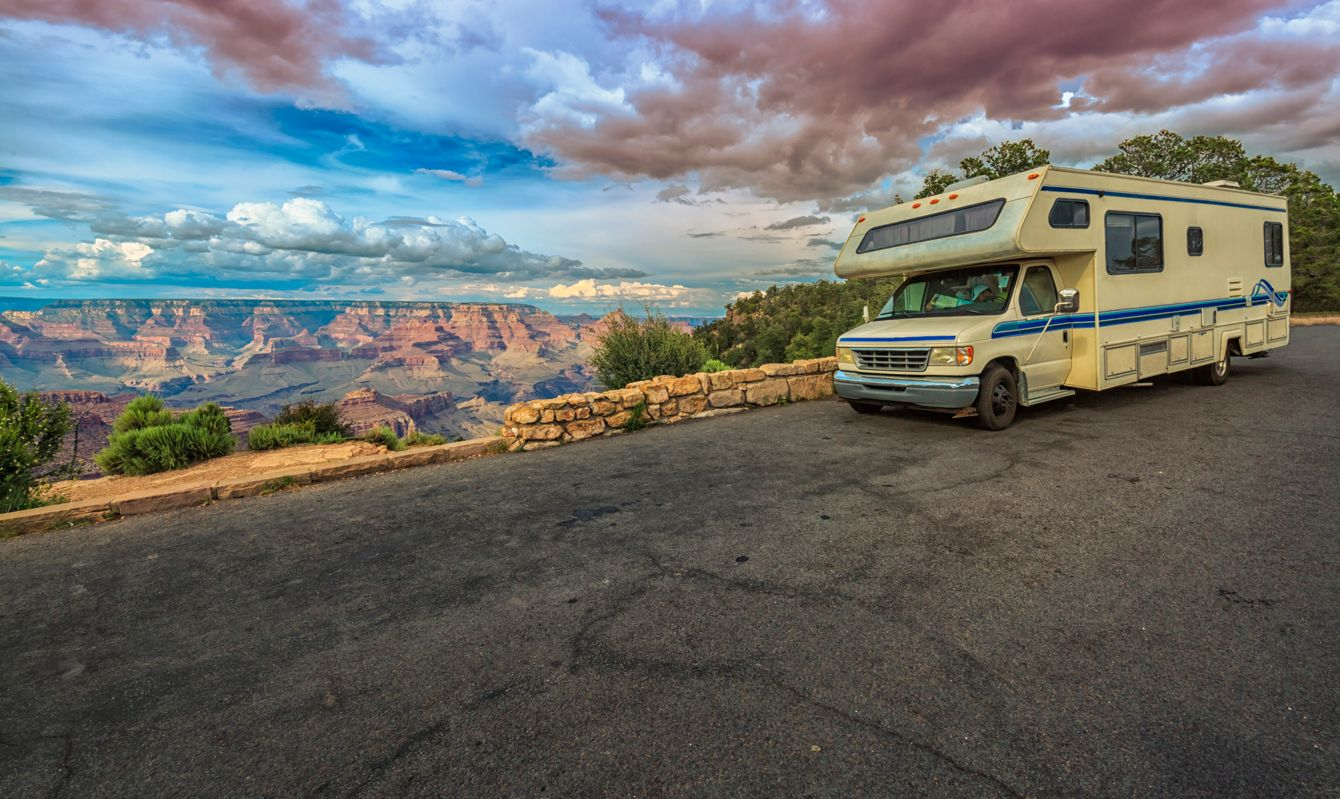 Magnificent view of the The Grand Canyon with RV making a stop in the mountain heights at sunset. Inside the vehicle a couple is checking a map.