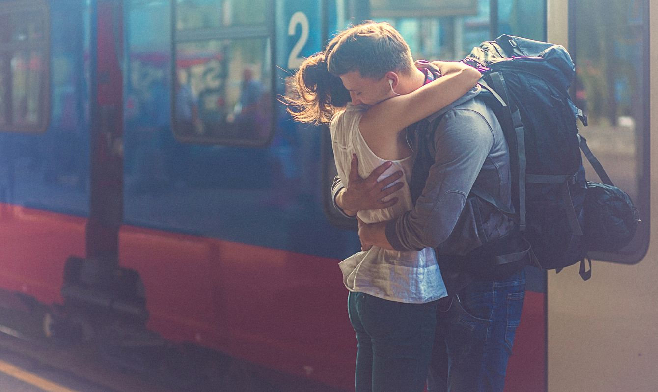 Close-up portrait of a woman and man at the railway platform, embracing and feeling in love. Romantic moment after a period of separation