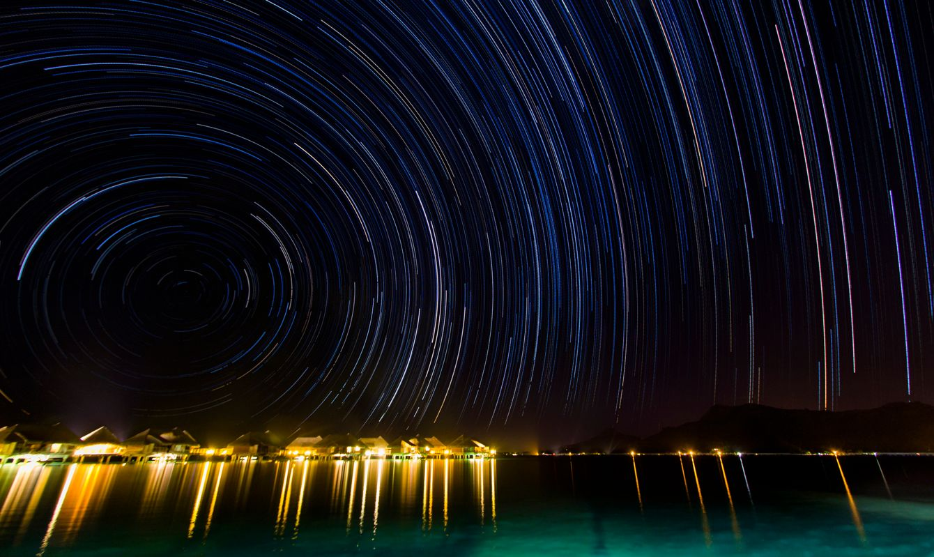 A DSLR long exposure photo forming a round startrail over Bora Bora in French Polynesia on a cloudless night. Across the tranquil waters of the lagoon are many overwater bangalows with their lights on casting long reflections over the surface. There is no one around.
