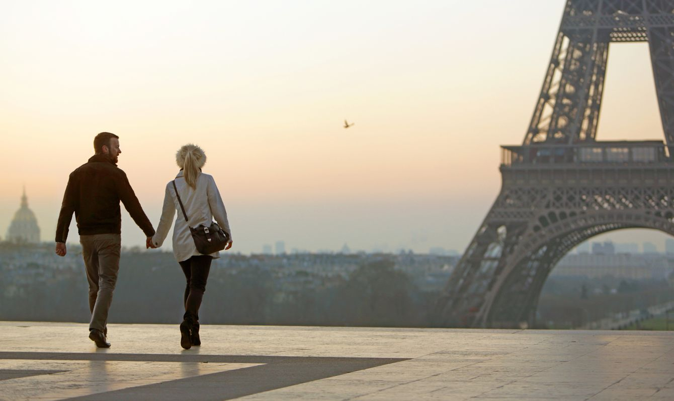 Couple holding hands, view of Eiffel Tower