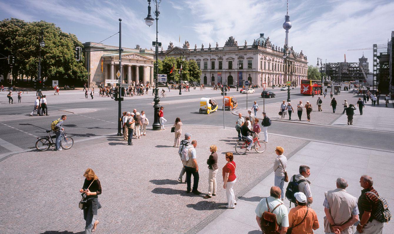 Large group of people at the famous Unten den Linden Boulevard, Berlin. Neue Wache and the Zeughaus (Deutsche Historischer Museum) in the background.