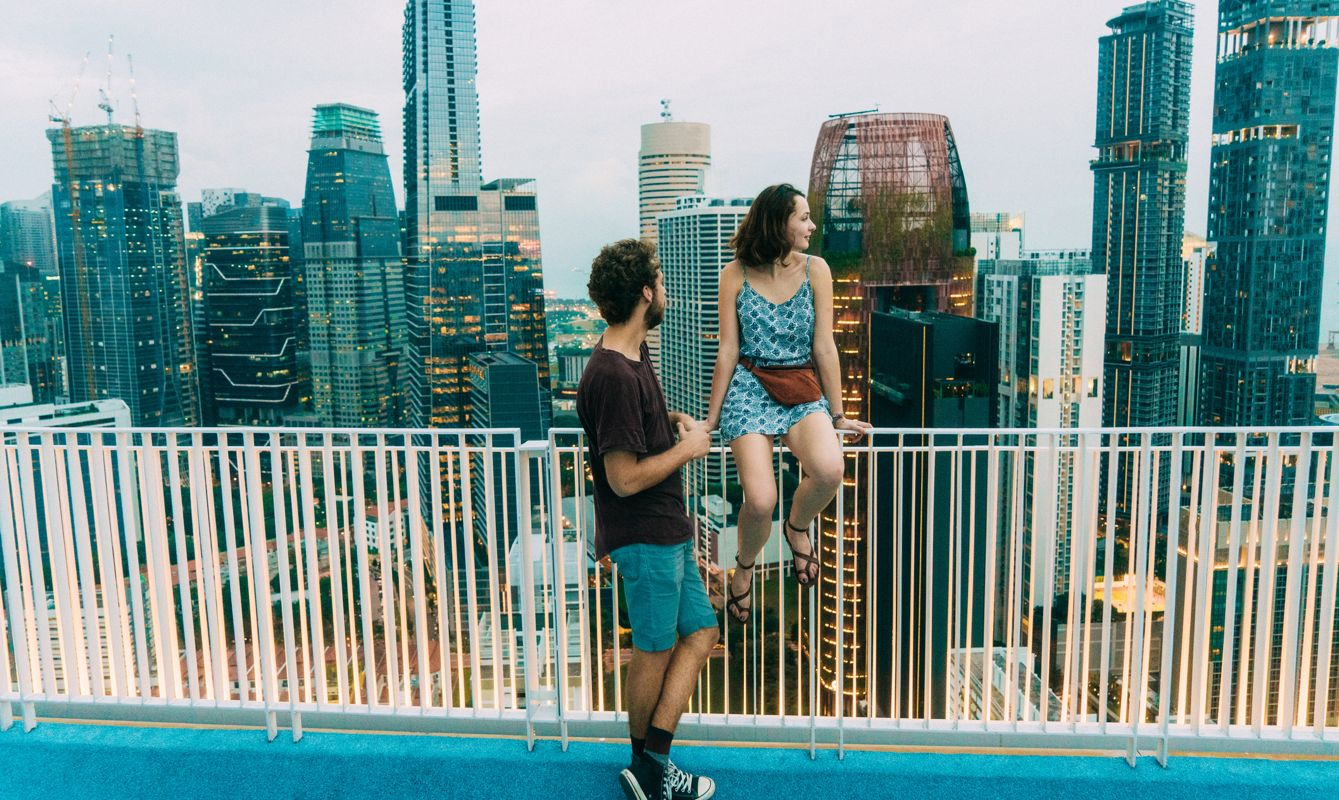 Young Caucasian couple looking at cityscape of Singapore city from view point