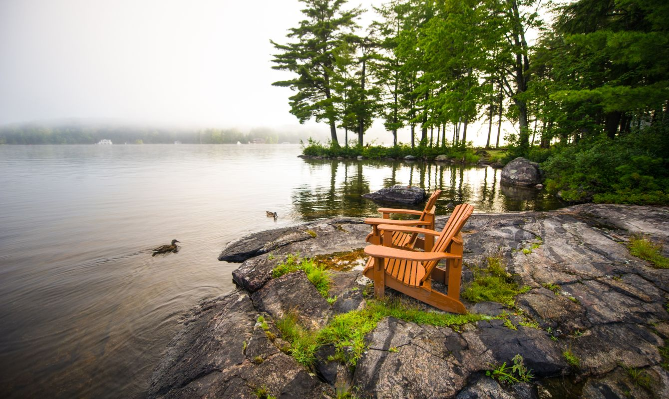 Adirondack chairs on a rock formation facing a calm lake. Ducks are in the water. The morning mist is covering part of the lake.